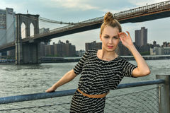 Young  lady outdoor on the pier with bridge on the background. Royalty Free Stock Photo