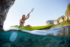 Young lady paddling the kayak. In a bay with limestone mountains. Split shot with underwater view stock photo