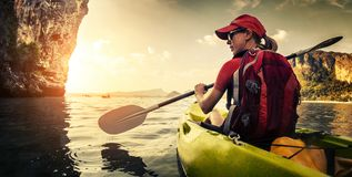 Young lady paddling kayak stock image