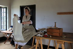 Young lady in period clothes, sewing clothes for soldiers, Fort Ticonderoga, New York, 2016 Royalty Free Stock Photo
