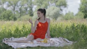 Young lady on picnic holding apple. Loop stock video