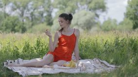 Young lady on picnic holding apple stock video footage