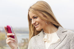 Young Lady with pink cell phone walking Stock Photo