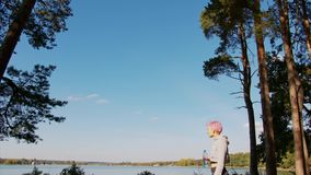 Young lady with pink hair jogging at the lake stock footage