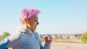 Young lady with pink hair jogging in the suburbs stock video footage