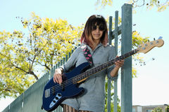 Young lady playing blue bass guitar outside Stock Photography