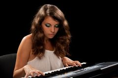 Young lady playing piano Stock Photos
