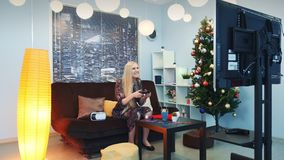 Young lady playing on playstation in front of TV at New Year`s Eve. There are VR glasses headset on sofa and Christmas tree in the room with skyscrapers in the stock video