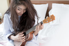 Young lady playing Ukulele in her bedroom Stock Photo