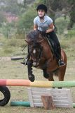 Young Lady on Pony jumping. Young teenager riding her pony and jumping over an obstacle Stock Photography