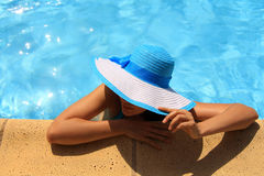 Young lady by the poolside. Young lady with white blue hat by the poolside Stock Image