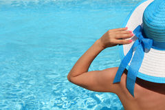 Young lady by the poolside. Young lady with white blue hat by the poolside Stock Images