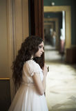 Young lady portrait. Dreaming young lady standing near opened door Stock Image