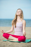 Young lady practicing yoga. Workout near ocean sea Royalty Free Stock Photos