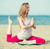 Young lady practicing yoga. Workout near ocean sea Stock Photos