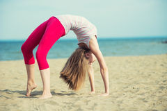 Young lady practicing yoga. Workout near ocean sea Royalty Free Stock Image