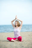 Young lady practicing yoga. Workout near ocean sea Stock Image