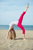 Young lady practicing yoga. Workout near ocean sea Royalty Free Stock Images
