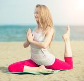 Young lady practicing yoga. Workout near ocean sea Royalty Free Stock Photo