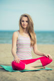 Young lady practicing yoga. Workout near ocean sea Stock Photography