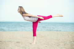 Young lady practicing yoga. Workout near ocean sea Royalty Free Stock Photography