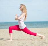 Young lady practicing yoga. Workout near ocean sea Stock Images