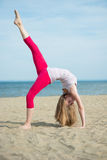 Young lady practicing yoga. Workout near ocean sea Stock Photo