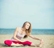 Young lady practicing yoga. Workout near ocean sea coast. Young lady practicing yoga. Beautiful woman posing at the summer sand beach. Workout near ocean sea Stock Images