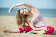 Young lady practicing yoga. Workout near ocean sea coast. Young lady practicing yoga. Beautiful woman posing at the summer sand beach. Workout near ocean sea Stock Photos