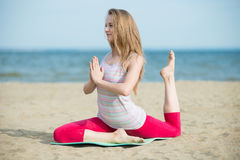 Young lady practicing yoga. Workout near ocean sea coast. Young lady practicing yoga. Beautiful woman posing at the summer sand beach. Workout near ocean sea Stock Photography