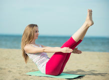 Young lady practicing yoga. Workout near ocean sea coast. Stock Images