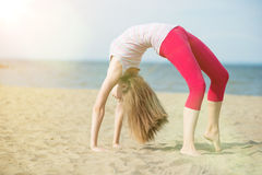 Young lady practicing yoga. Workout near ocean sea coast. Royalty Free Stock Image