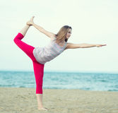 Young lady practicing yoga. Workout near ocean sea coast. Stock Image
