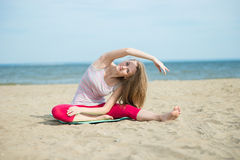 Young lady practicing yoga. Workout near ocean sea coast. Royalty Free Stock Images
