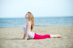 Young lady practicing yoga. Workout near ocean sea coast. Royalty Free Stock Photo