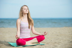 Young lady practicing yoga. Workout near ocean sea coast. Young lady practicing yoga. Beautiful woman posing at the summer sand beach. Workout near ocean sea Royalty Free Stock Photos