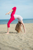 Young lady practicing yoga. Workout near ocean sea coast. Young lady practicing yoga. Beautiful woman posing at the summer sand beach. Workout near ocean sea Stock Photo