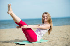 Young lady practicing yoga. Workout near ocean sea coast. Royalty Free Stock Photography