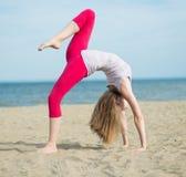 Young lady practicing yoga. Workout near ocean sea coast. Stock Photos