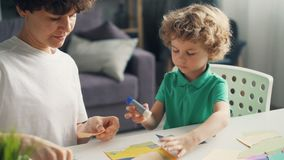 Young lady teaching her son make collages using paper, glue stick and scissors. Young lady professional designeer is teaching her son to make collages using stock footage