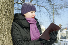Young lady reading book. Outdoors at winter time Royalty Free Stock Photo
