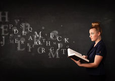 Young lady reading a book with alphabet letters Royalty Free Stock Images