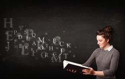Young lady reading a book with alphabet letters Stock Photos