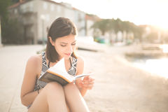 Young lady reading a book on a beach at sunset Stock Photography