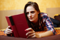 Young lady reading a book on the bed Stock Photos