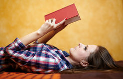 Young lady reading a book on the bed Stock Photography