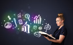 Young lady reading a book with business icons. Coming out of the book Royalty Free Stock Photo