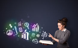 Young lady reading a book with business icons. Coming out of the book Stock Photography