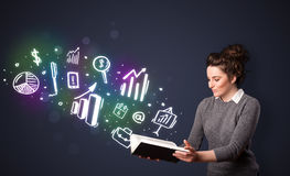 Young lady reading a book with business icons Royalty Free Stock Photography