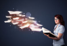 Young lady reading a book with flying sheets coming out of the b Royalty Free Stock Photography